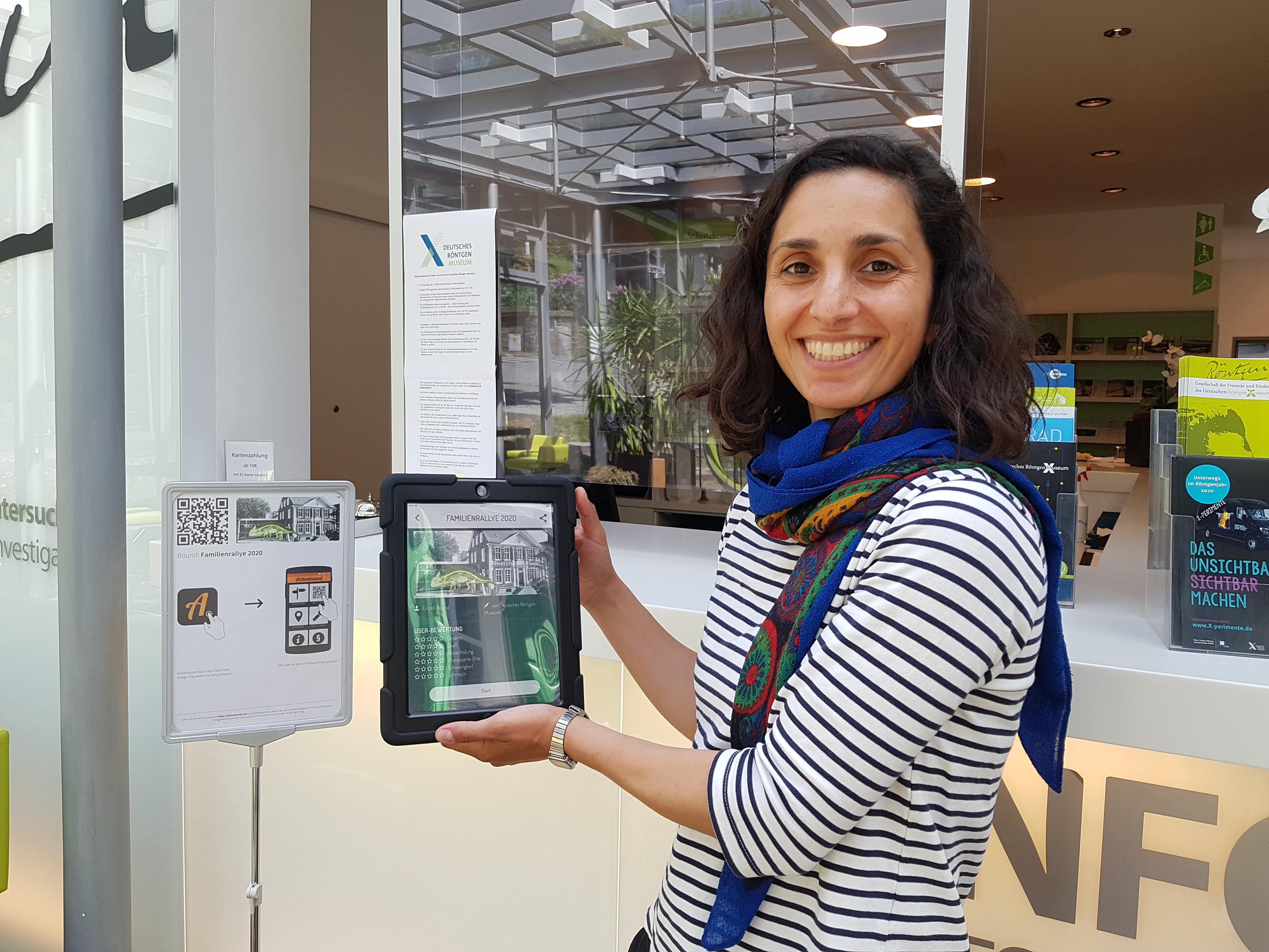 Frau mit Tablet in der Hand im Foyer des Röntgen Museums im Hintergrund ein Bild mit dem Actionbound Logo